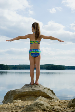 one girl only: Girl standing on rock by lake Stock Photo