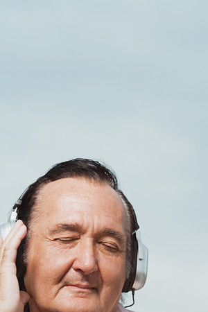 confortable: Senior man listening to headphones