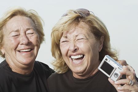 mujer alegre: Mujeres de risa con cámara digital Foto de archivo