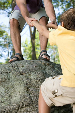onto: Father pulling son onto rock
