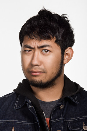 raised eyebrow: Portrait of young adult Asian man