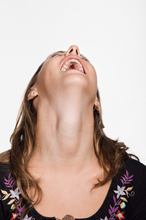 Portrait of young woman with her head back laughing Banco de Imagens