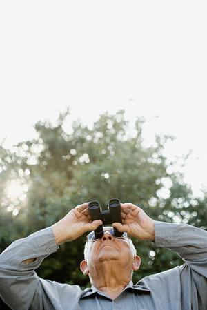 active retirement: Senior man looking through binoculars