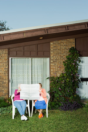 broadsheet newspaper: Two senior women sharing a newspaper Stock Photo