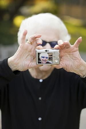 one senior adult woman: Senior woman taking a self portrait photograph