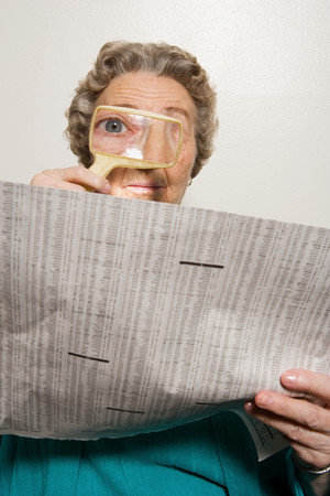 broadsheet newspaper: Woman reading newspaper with magnifying glass
