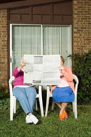oude krant: Two senior women sharing a newspaper Stockfoto