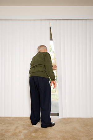 snooping: Elderly man looking out of blinds