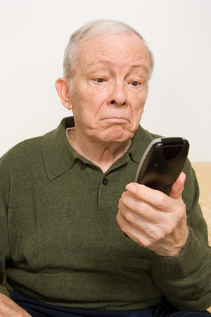 channel surfing: Elderly man with remote control Stock Photo