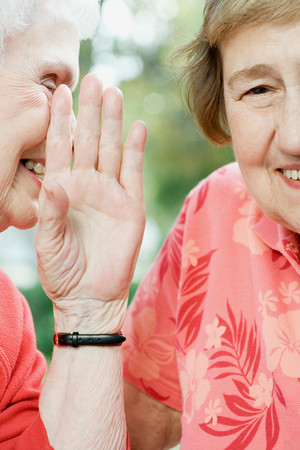individually: Two senior women sharing a secret Stock Photo