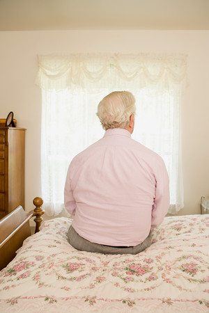 personas sentadas: El hombre mayor sentado en la cama