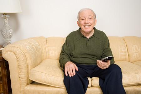 sitting man: Elderly man on sofa with remote control Stock Photo