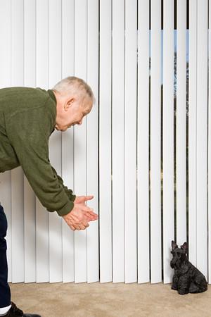 beckoning: Elderly man beckoning dog ornament Stock Photo