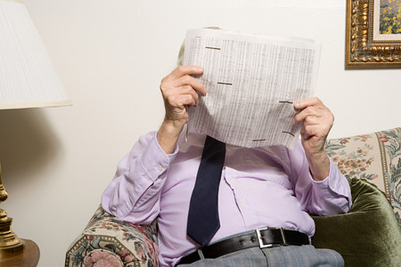 broadsheet newspaper: Senior man reading a newspaper