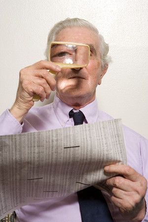 broadsheet newspaper: Man reading newspaper with magnifying glass