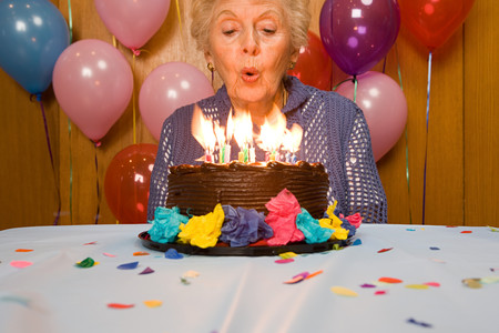 elderly: Senior woman blowing out candles on cake Stock Photo