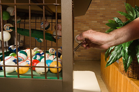 caller: Bingo caller reaching for a bingo ball Stock Photo