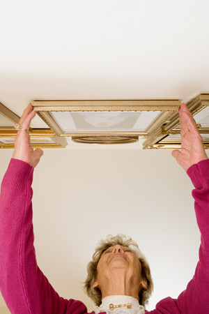 perfectionist: Woman adjusting picture frames
