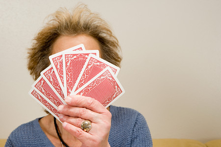 concealment: Senior woman holding playing cards Stock Photo