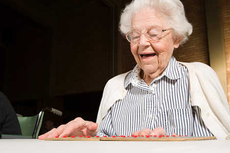 personas sentadas: Senior woman playing bingo
