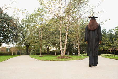 jamaican adult: Female graduate walking down a path Stock Photo