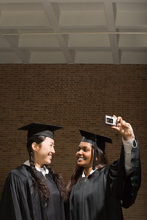 Two female graduates taking a photograph Stock Photo