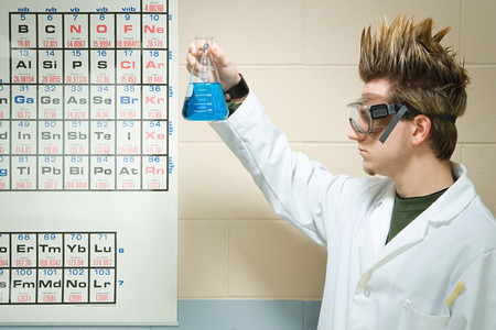 Male student holding up a chemical liquid