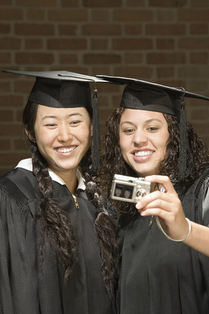 chinese american ethnicity: Two female graduates taking a photograph Stock Photo