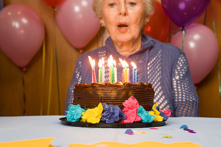 blowing out: Senior woman blowing out candles on cake Stock Photo