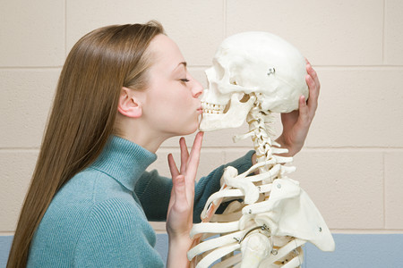 Female student kissing a human skeleton