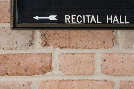 recital: Recital hall sign on brick wall