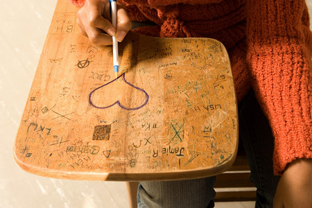 misbehaving: Student drawing a heart on her desk Stock Photo