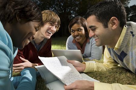 personas sentadas: Cuatro estudiantes estudian al aire libre Foto de archivo