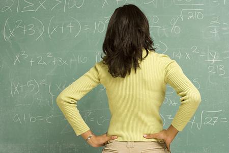 jovenes estudiantes: Estudiante femenino de pie delante de la pizarra
