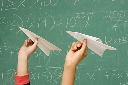 throw paper: Two students about to throw paper aeroplanes