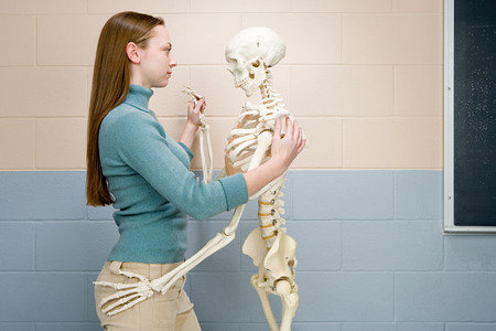 teenager girl: Female student dancing with human skeleton