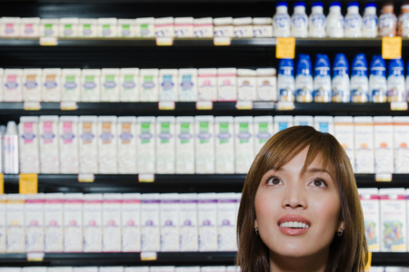 Young woman shopping in a supermarket Imagens