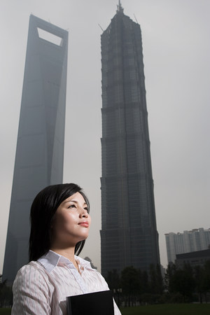 capable of learning: Chinese woman near skyscrapers Stock Photo