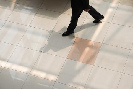 waist down: Businessman walking on tiled floor