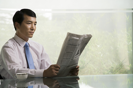 current events: Chinese businessman reading a newspaper Stock Photo