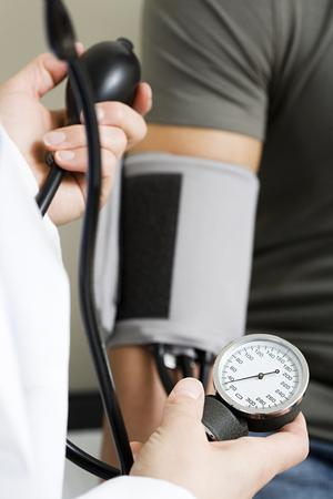 blood pressure monitor: Taking blood pressure reading Stock Photo
