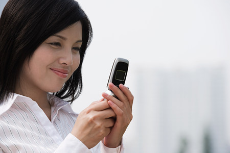 capable: Chinese businesswoman text messaging