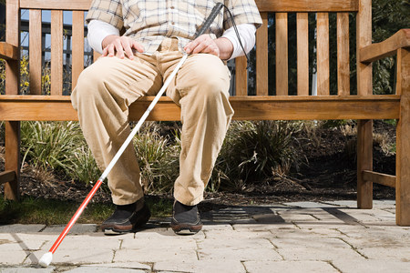 Blinde man zittend op een bankje
