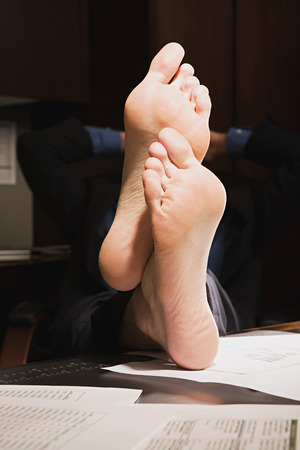 one mid adult man: Businessman with feet up on desk Stock Photo