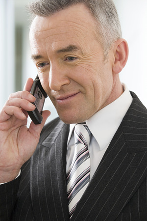 cellular telephone: Mature businessman using a cellular telephone Stock Photo
