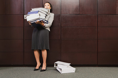 office chaos: Businesswoman struggling with heavy files Stock Photo