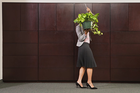 Business woman carrying plant Stock Photo