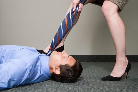 dominacion: Mujer que tira de la corbata de gerente Foto de archivo