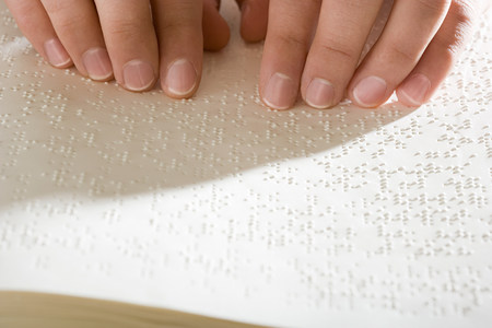 overcoming adversity: One woman reading braille Stock Photo