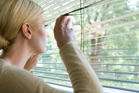 looking at: Woman looking out of blinds